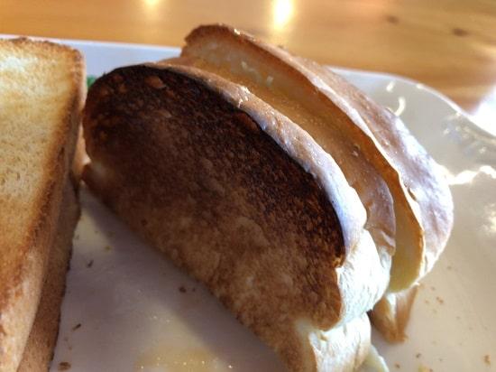 コメダ珈琲店 - あみ焼きホットチキンサンドの一切れ写真